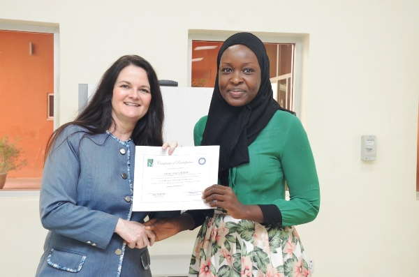 President Dekle presents Alumni College workshop certificate to Ms.  Amal Babangida Sabo